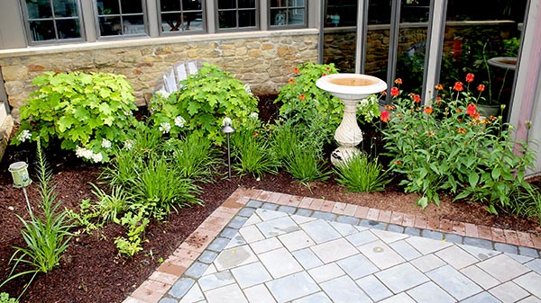 Paver patio corner next to garden grand rapids